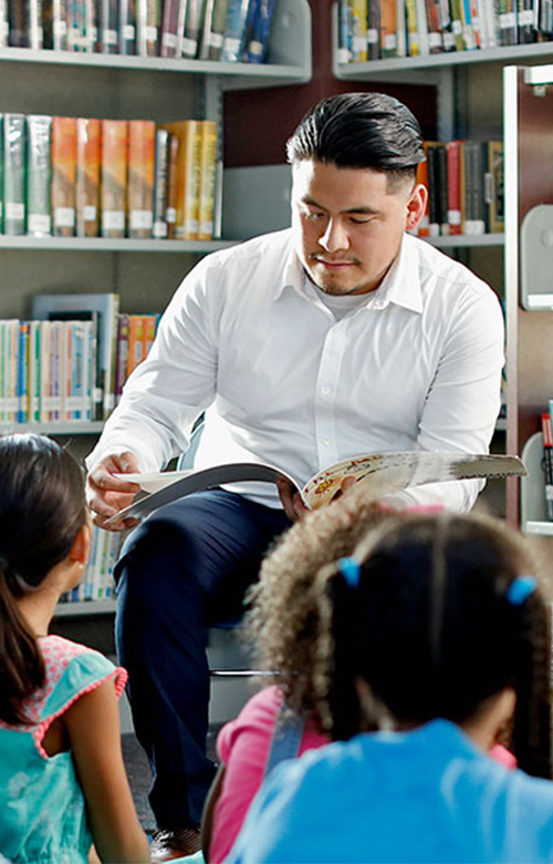 Teacher reading to children in library