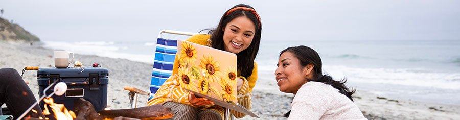 Krystal F. - Class of 2021, at beach with laptop and friend